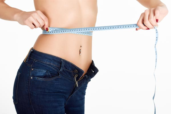 woman measuring waist instead of weighing every day